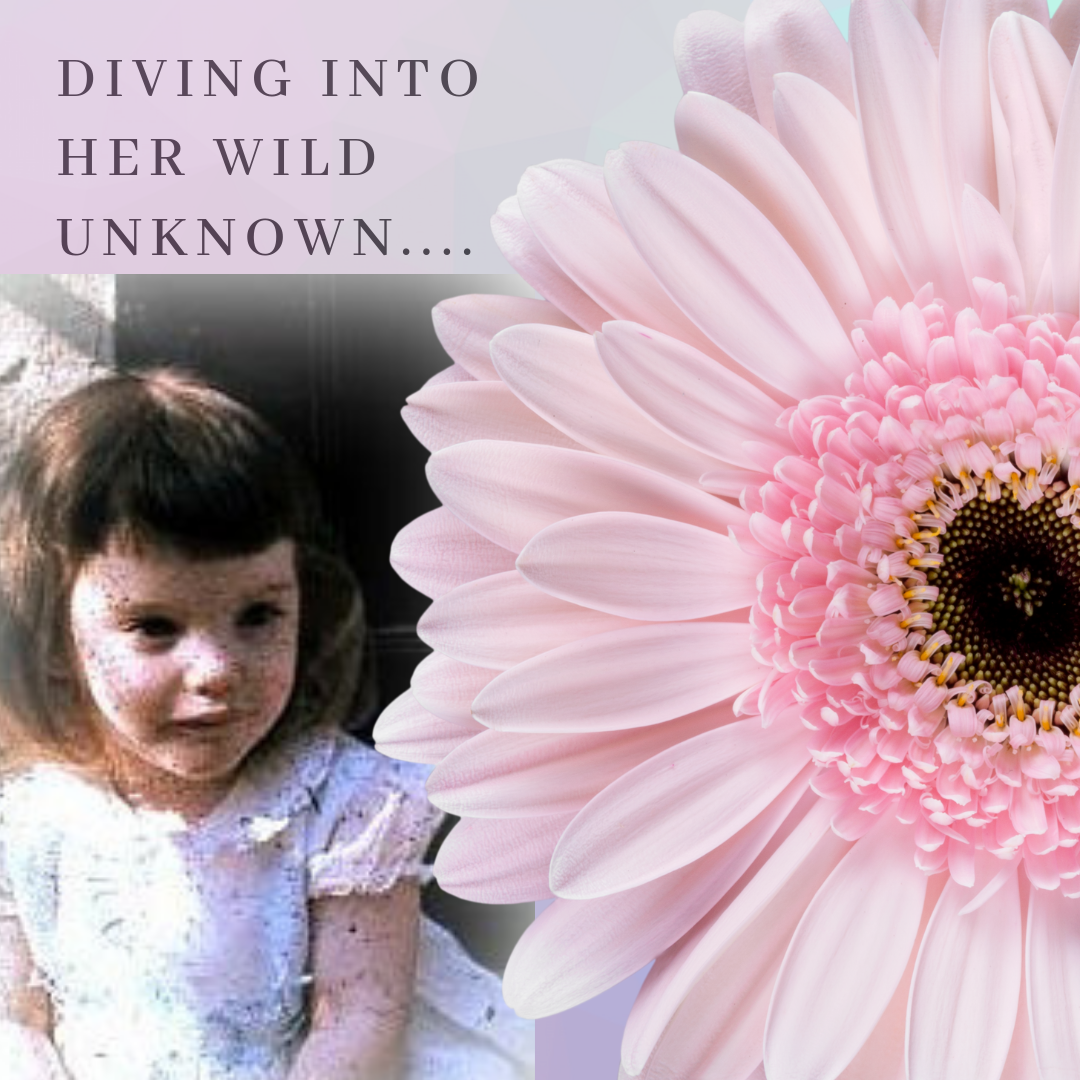 A two-year old girl wearing clothes from the early 1960's sits contemplatively beside a large pink flower.