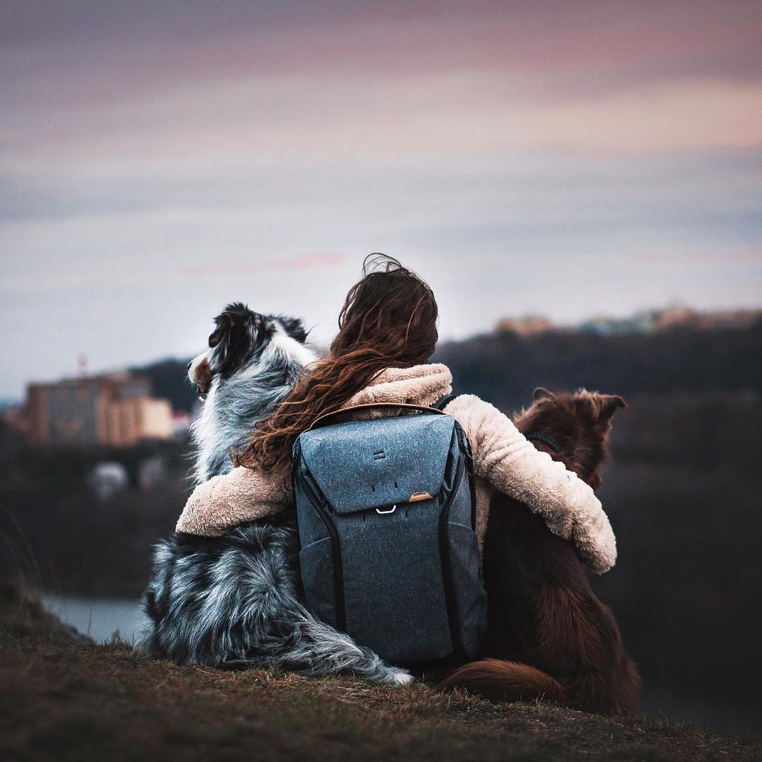 a woman with wearing a backpack with her arms around 2 dogs