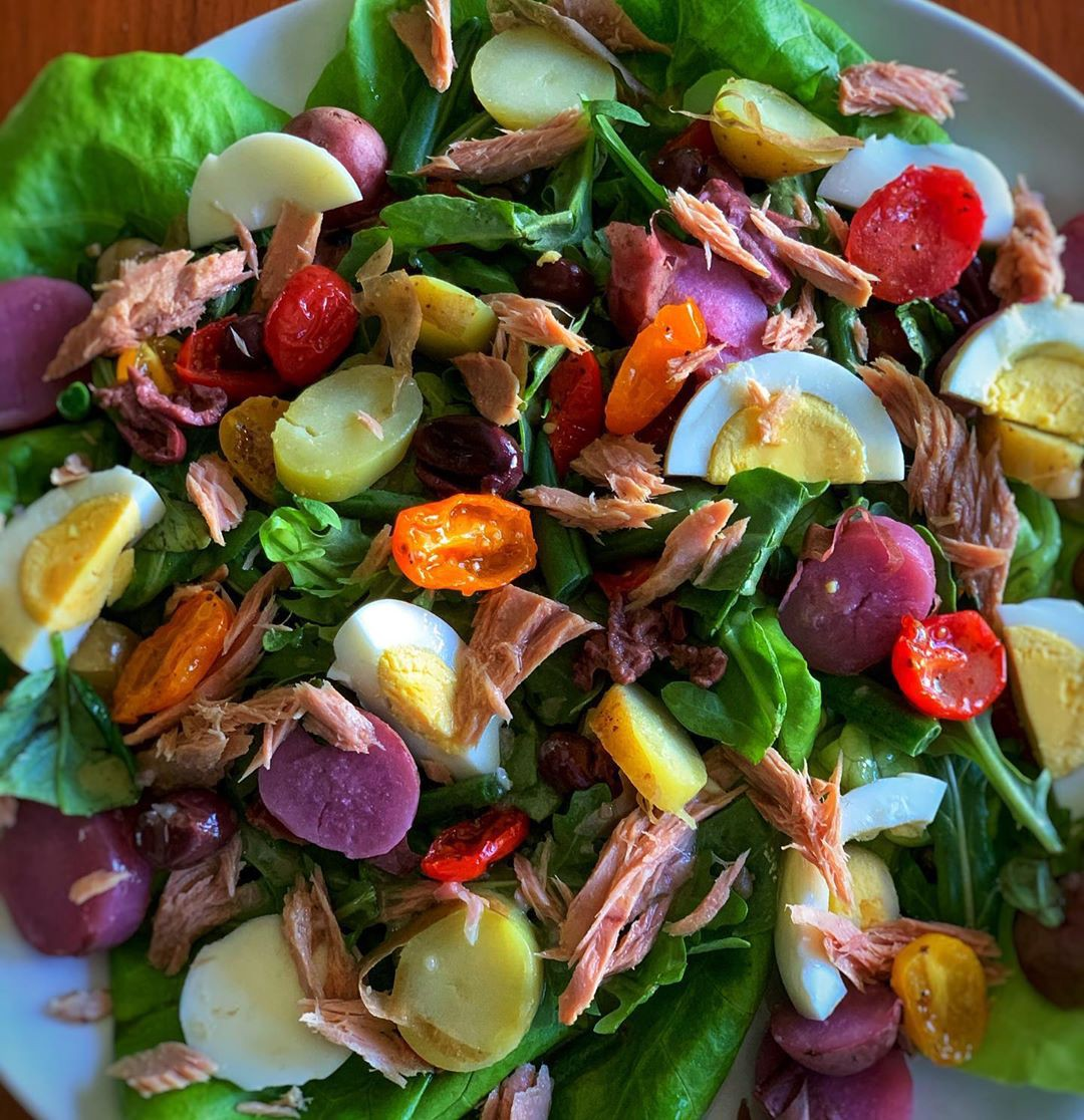 A plate piled high with a vibrant salad containing ingredients like sliced boiled eggs, cherry tomatoes, and shreds of meat.