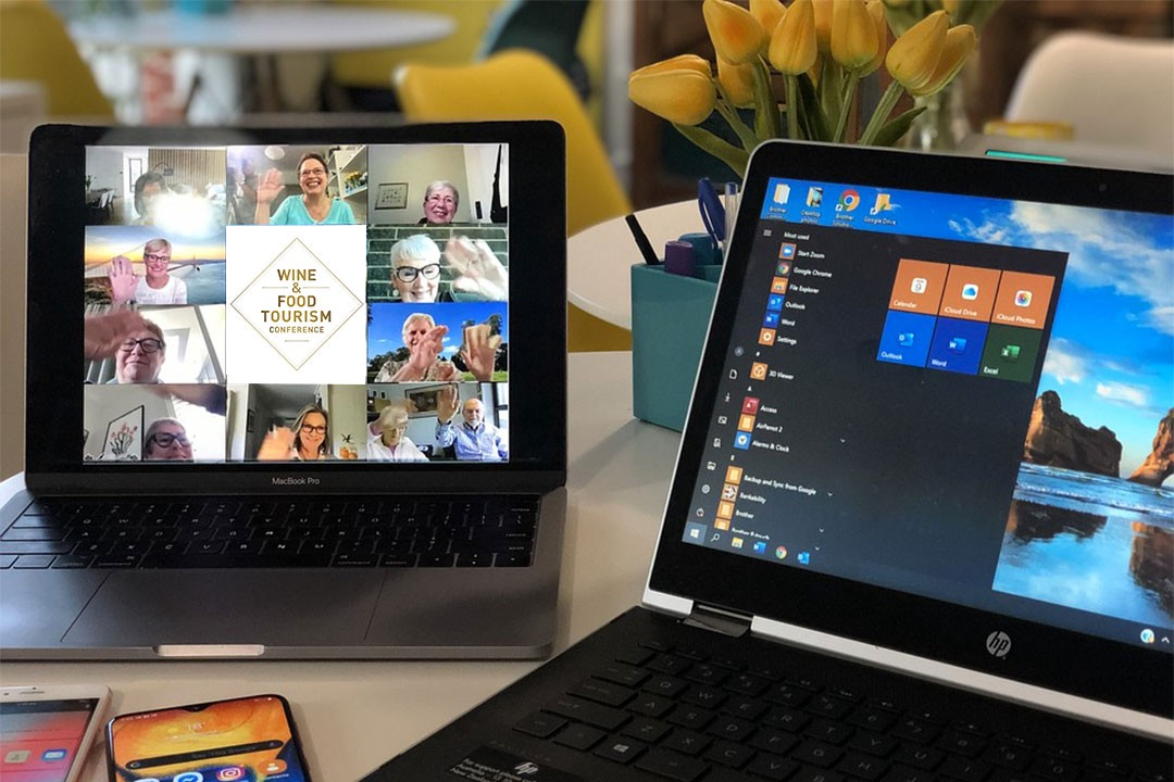 A tablet and laptop displaying an online conference