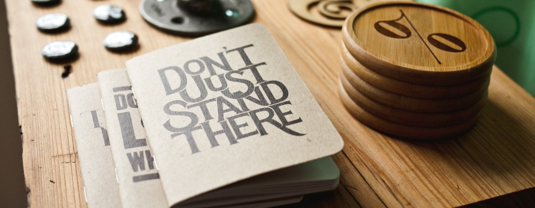 "A pamphlet entitled ""Don't Just Stand There"" sits on a wooden desk"