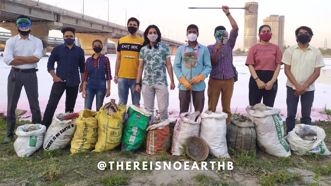 9 There Is No Earth B volunteers stand at Yamuna river bank with 11 bags of collected waste placed in front of them
