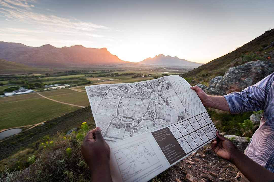 Hands holding a La Motte hiking trail map with scenic wine farm view