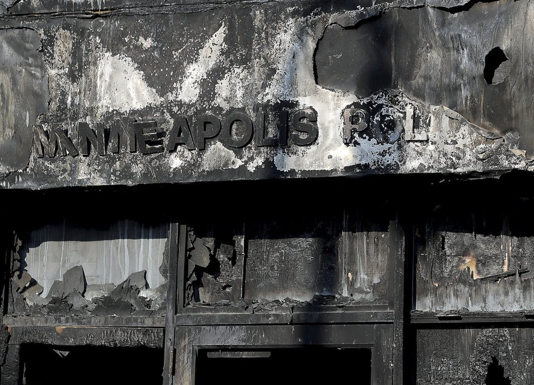 "A Minneapolis police station, charred and burned. The letters ""Minneapolis pol"" are barely distinguishable"