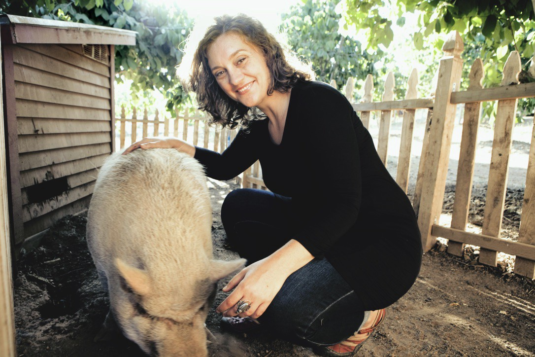 Brianne Donaldson kneels in a pen, petting a pig
