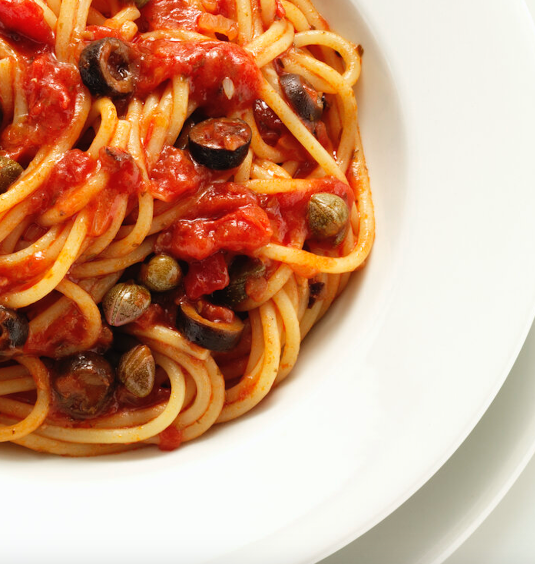Closeup of a shallow dish of spaghetti with tomato sauce, studded with capers and slices of black olives.