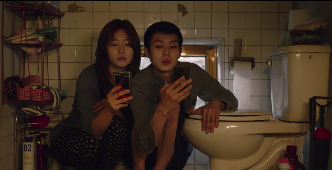 Park So-dam and Choi Woo-shik on their phones in their tiny apartment, perched on the ledge with their toilet