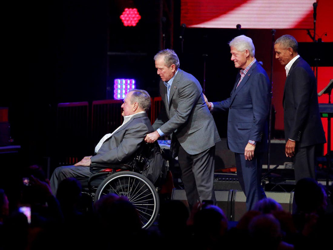 George W. Bush pushes his father, George H.W. Bush, in a wheelchair as Bill Clinton and Barack Obama look on.