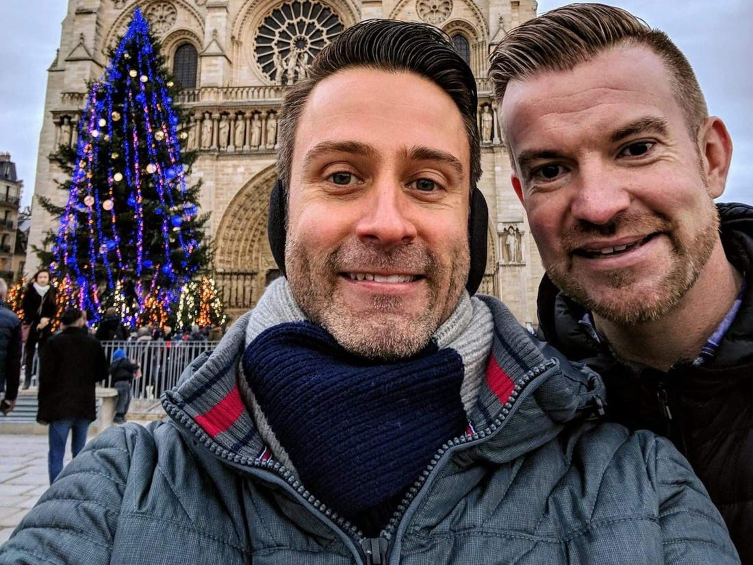 Chris Good and his partner are seen in front of the Notre Dame Cathedral in Paris after their move to France in 2017.