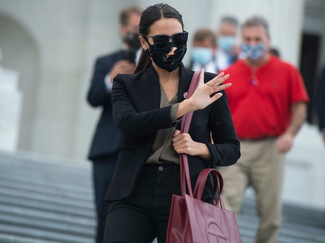 "AOC wore the Telfar Shopping Bag in the color ""Oxblood."""