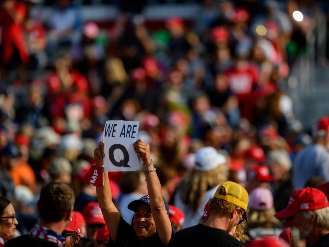 A person with a QAnon sign at a rally.
