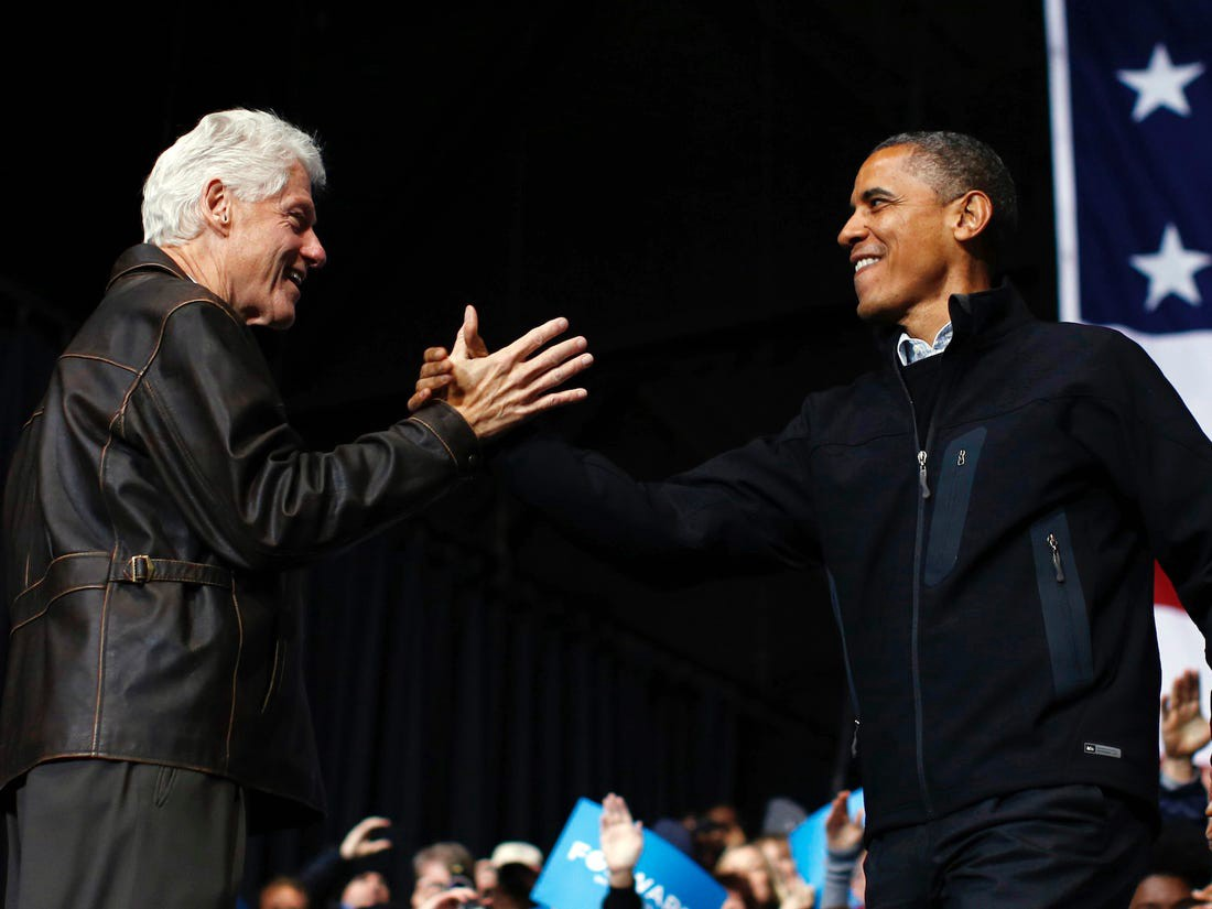 Bill Clinton and Barack Obama greet each other.