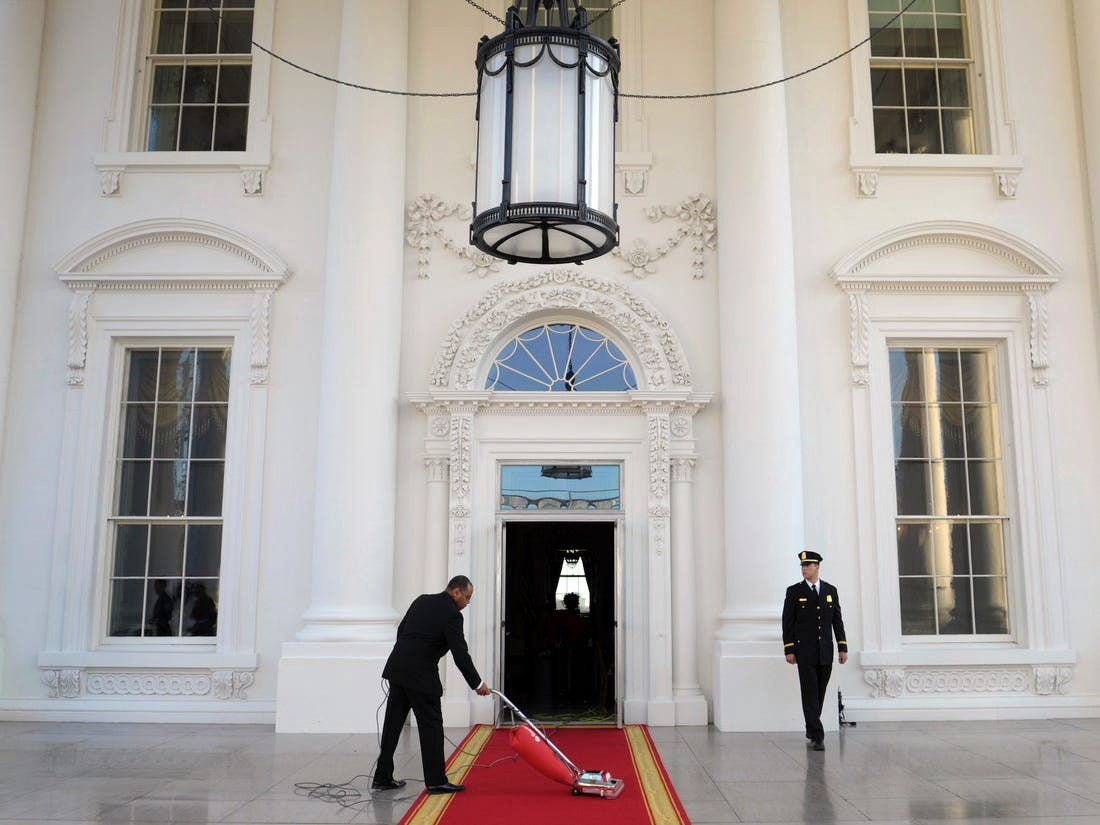 A man cleans outside the White House.