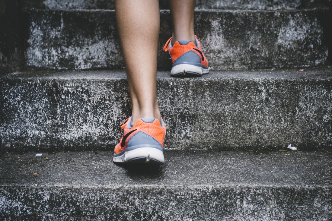 The ankles and calves of a woman in running shoes climb up stone steps.