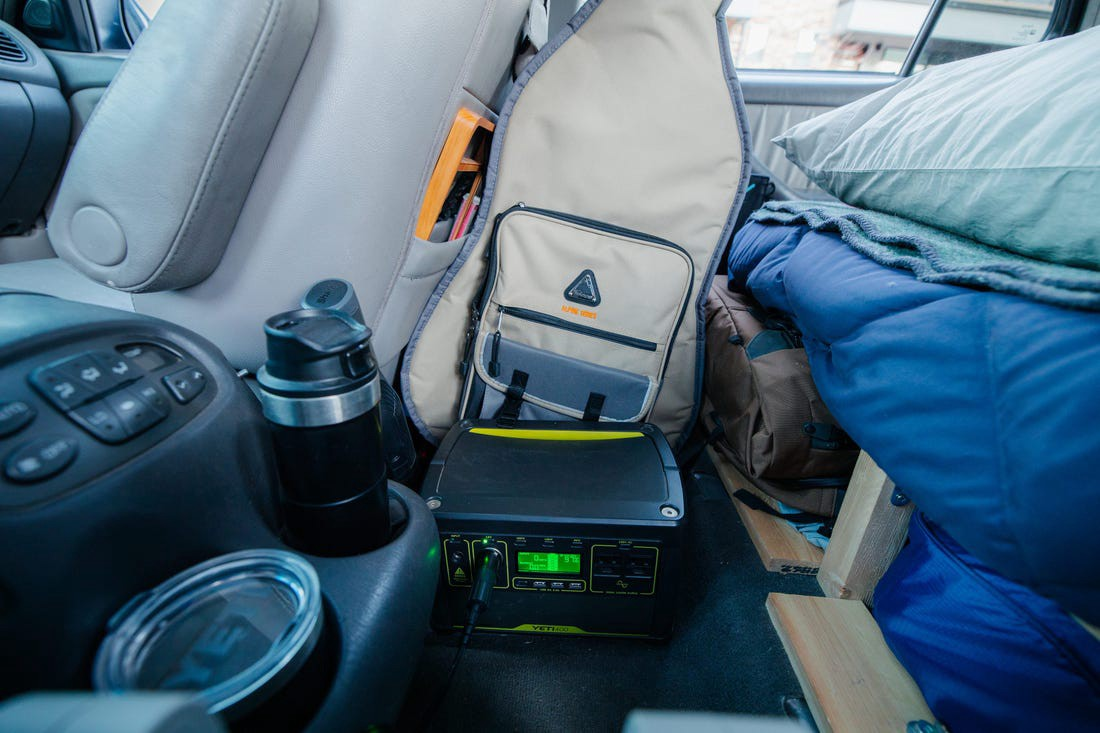 The battery and guitar in the back of the car.