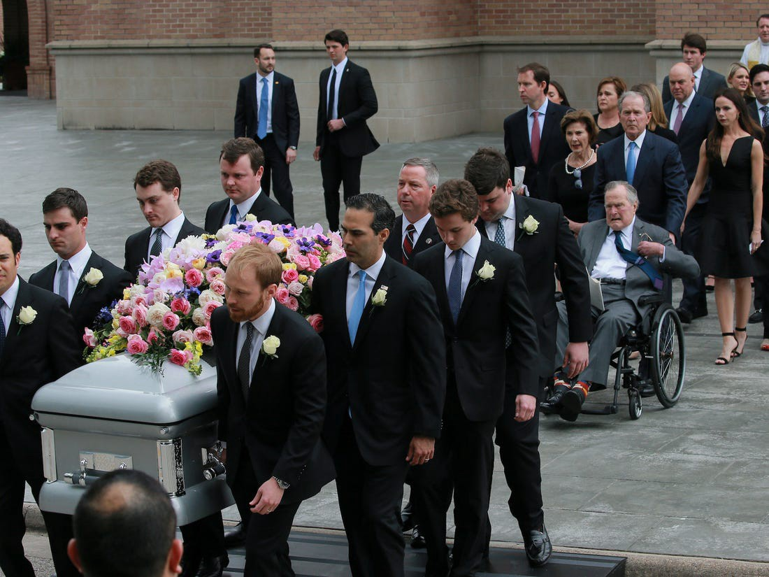 The Bush family are seen behind a casket.