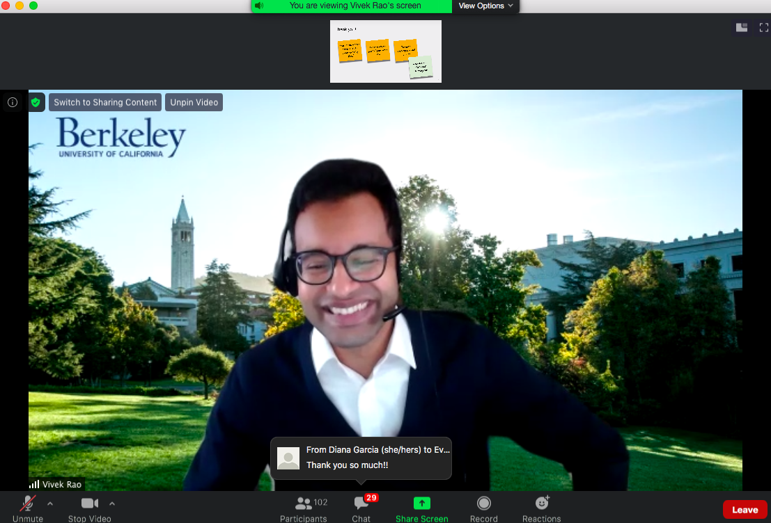 Screenshot of a Zoom call with a dark-haired man in glasses and a blue sweater smiling.