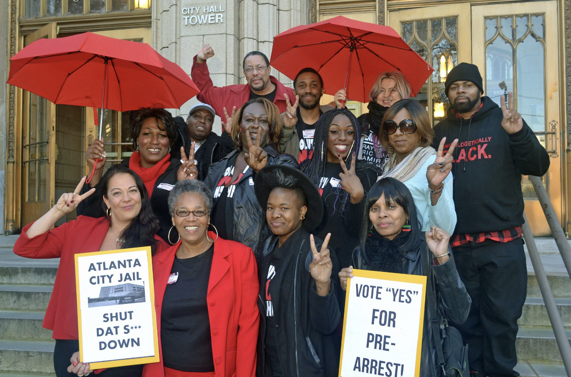 """Organizers stand in front of City Hall with red umbrellas, red & black shirts with protest signs, """"Vote YES for pre-arrest!"""""""