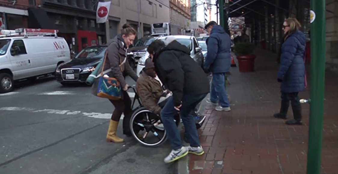 Two individuals helping someone in a wheelchair up onto the sidewalk from the street