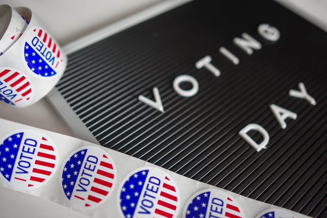 A black board saying Voting Day and a ribbon of American flag stickers which say I voted.
