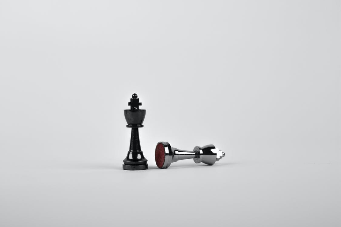 Two silver chess pieces on silver background