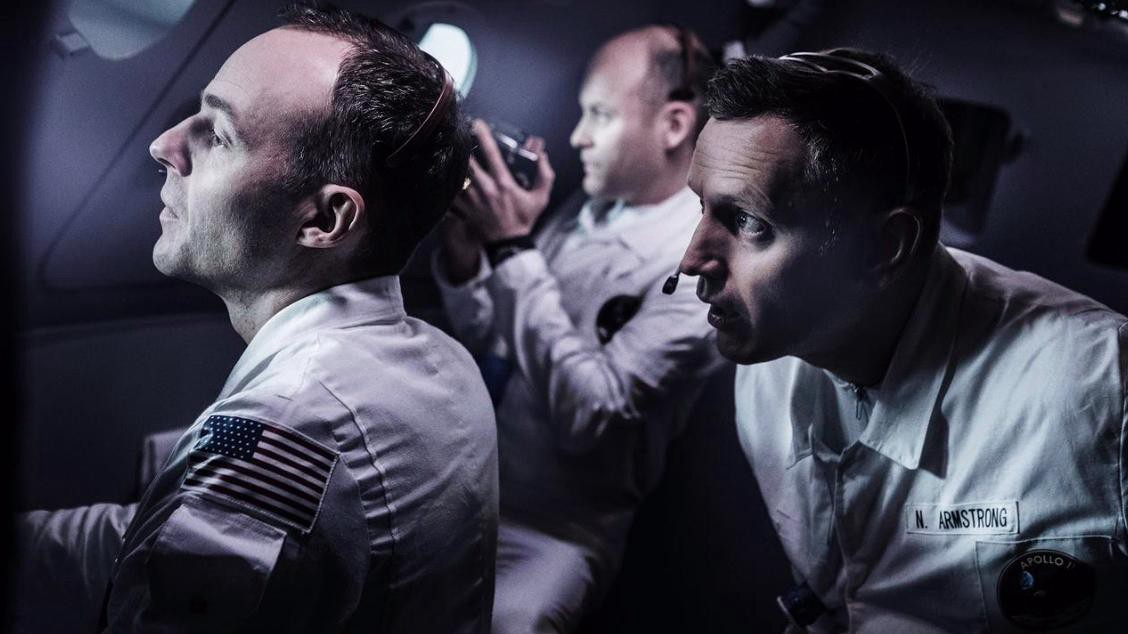 Three lead characters, including Aldrin, staring out of their ship into space.