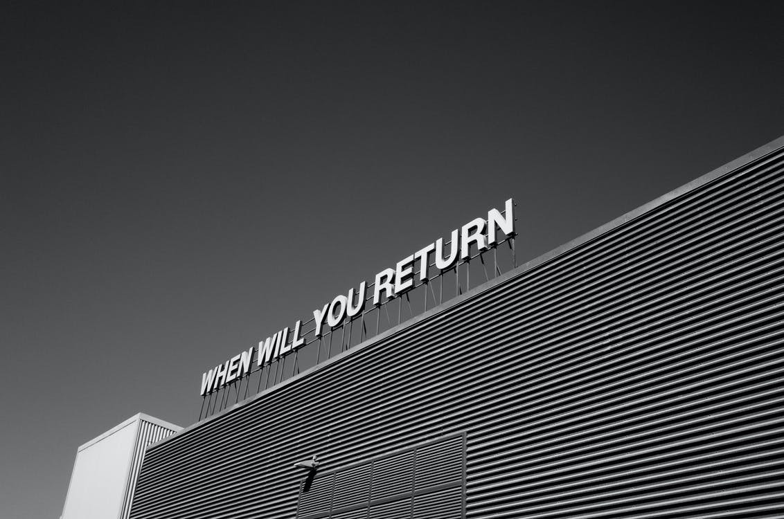 """Black and white image of building that reads """"when will you return"""""""
