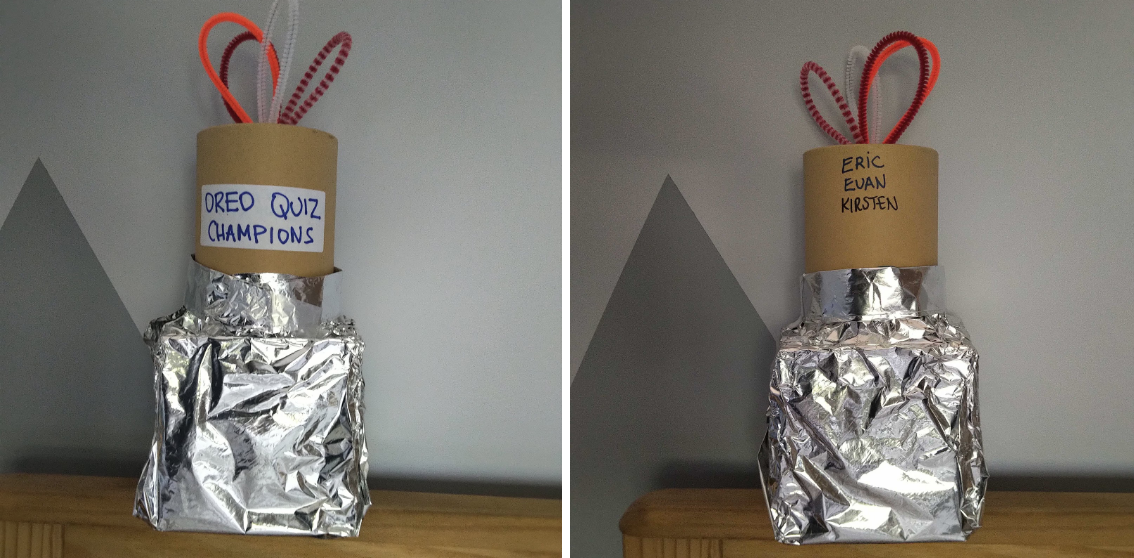 Two views of a home made trophy with a cardboard cylinder top, square foil bottom, and coloured pipe cleaners stuck on top