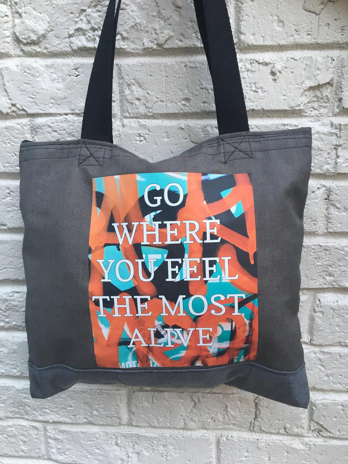 "Tote bag with message that reads ""Go where you feel the most alive."""