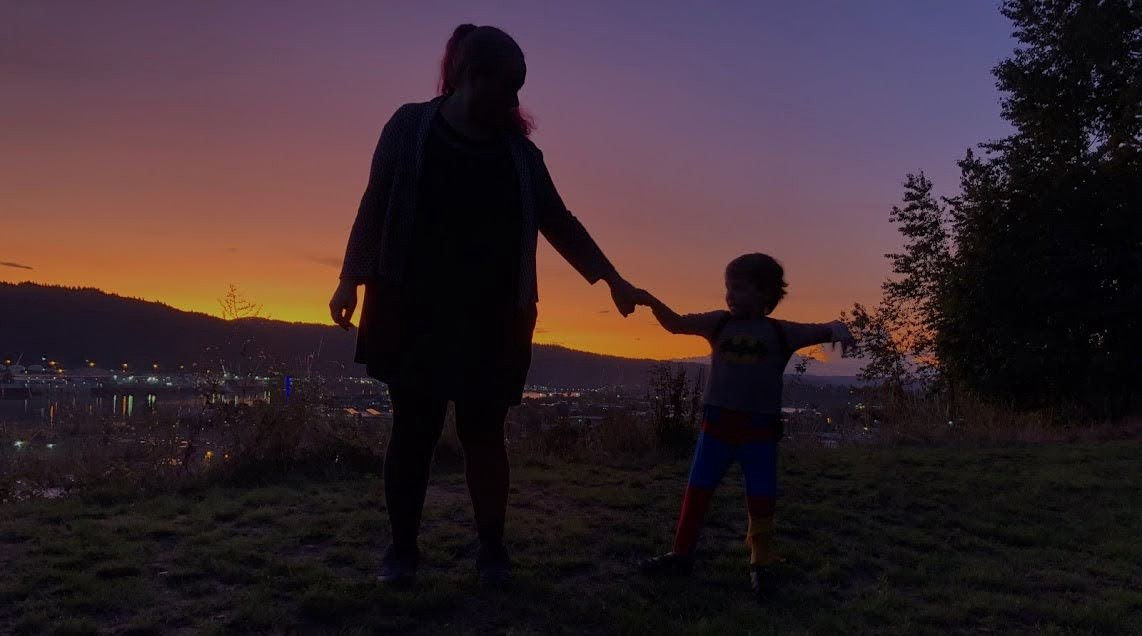 The author and her young son holding hands at dusk with the last bits on sunset in the distant background.