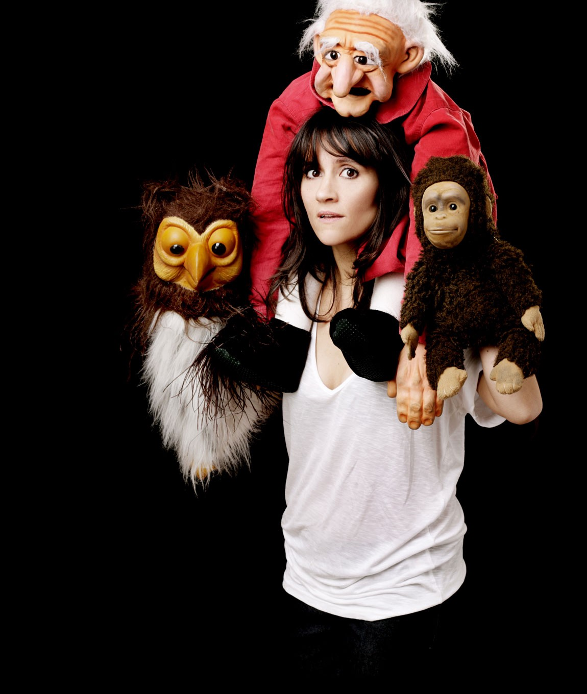 Nina Conti surrounded by her best-known puppets, the monkey, the old man and the owl.