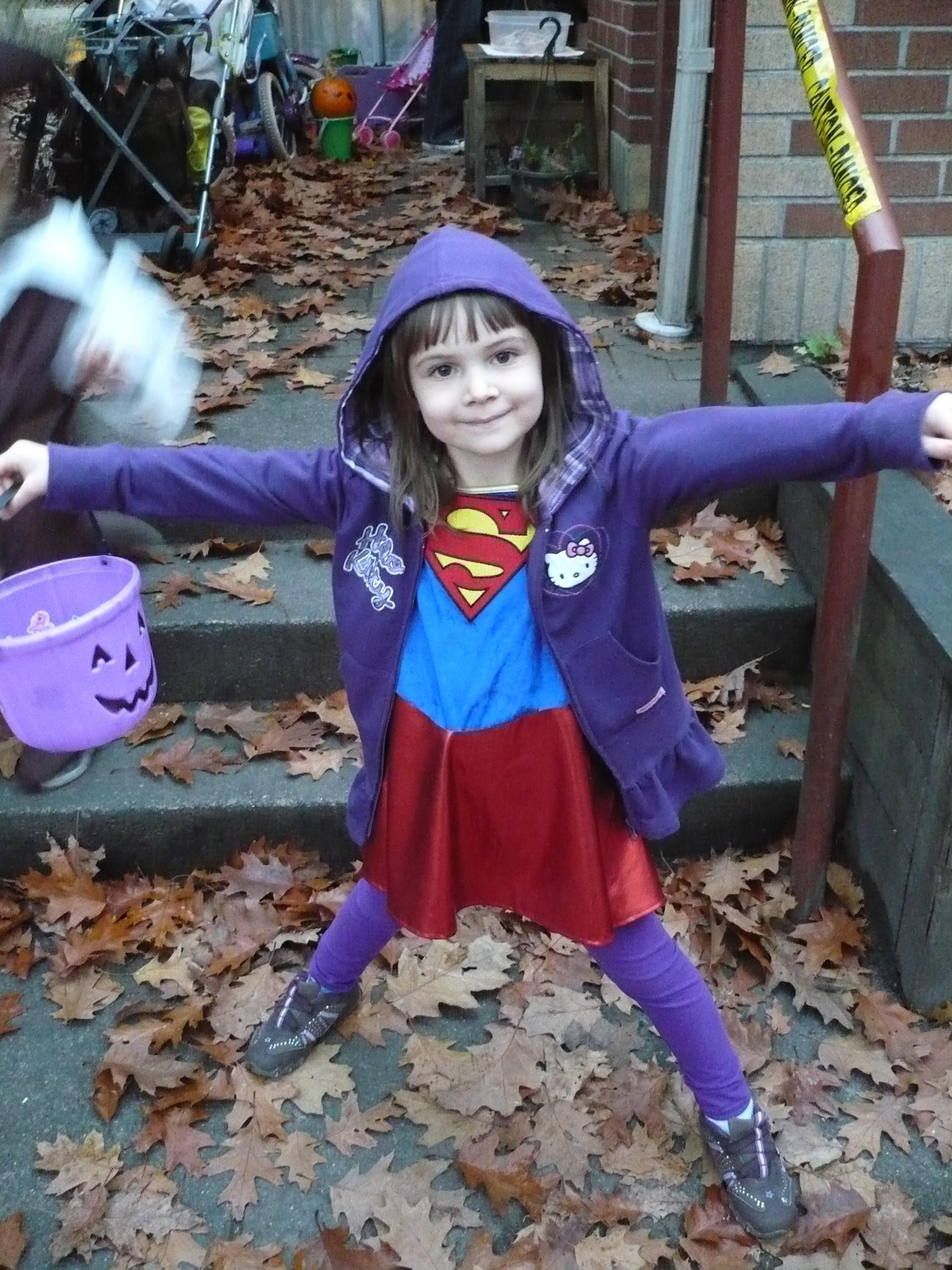 Girl wearing a Superman costume and holding a purple pumpkin container