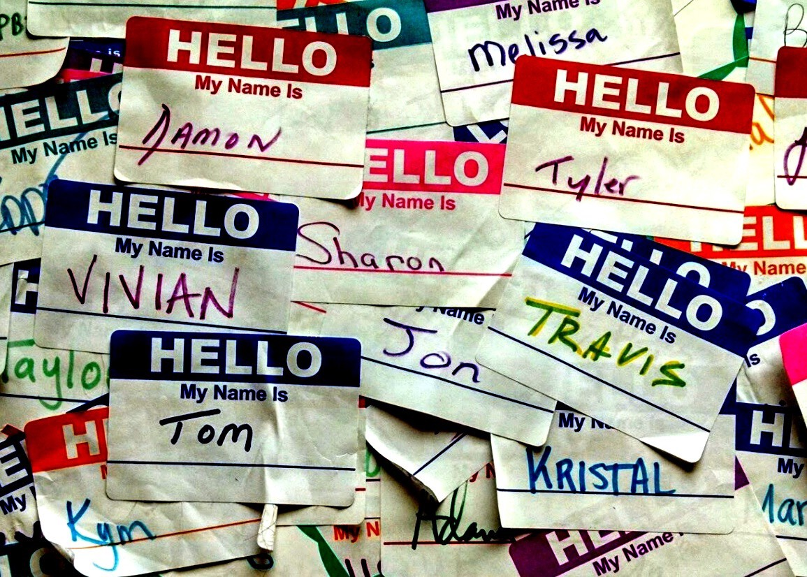 """A collage of """"Hello My Name Is"""" stickers with names such as: Damon, Sharon, Tom, Jon, Vivian, Travis, and Kristal."""