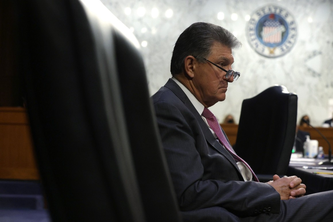 Profile view of West Virginia Senator Joe Manchin in a navy blue suit and purple tie, slouched down in a chair in a Senate Committee room with glasses balanced on the end of his nose, seemingly thinking about how he isn't going to do his Constitutional duty to protect people's voting rights and our nation's democracy.