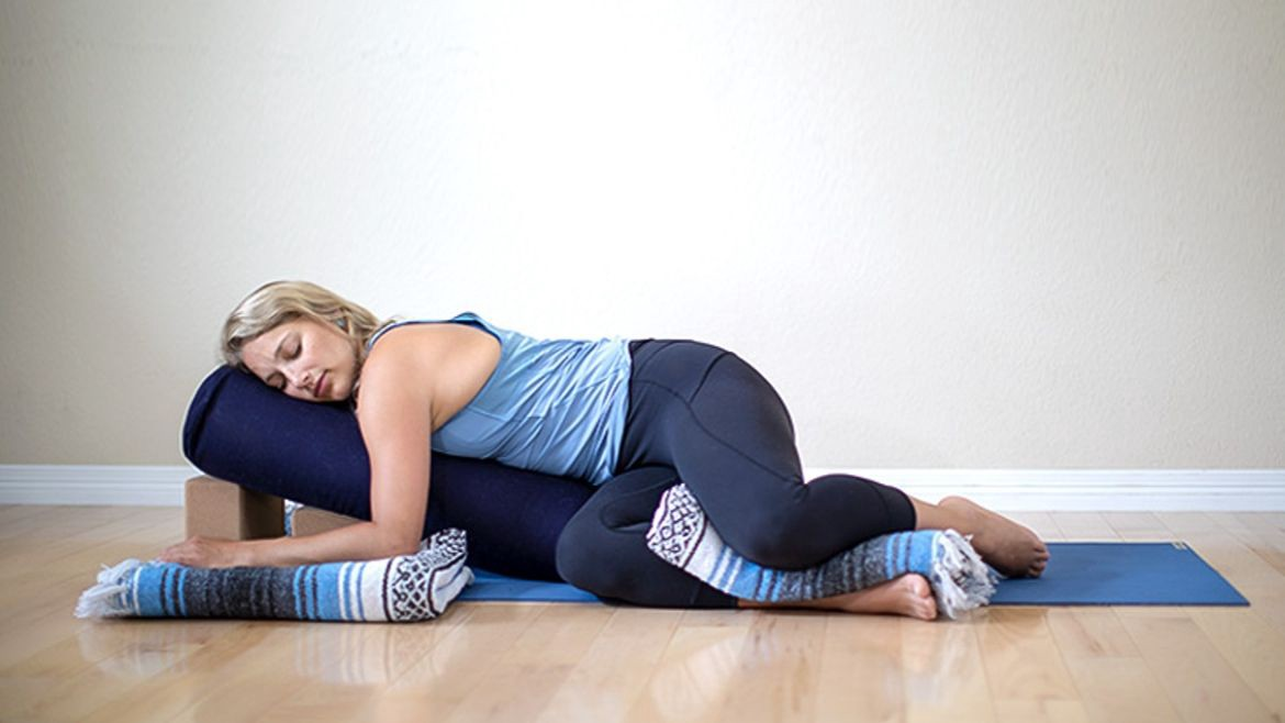 A woman practising yoga with pillows, blocks and blankets.