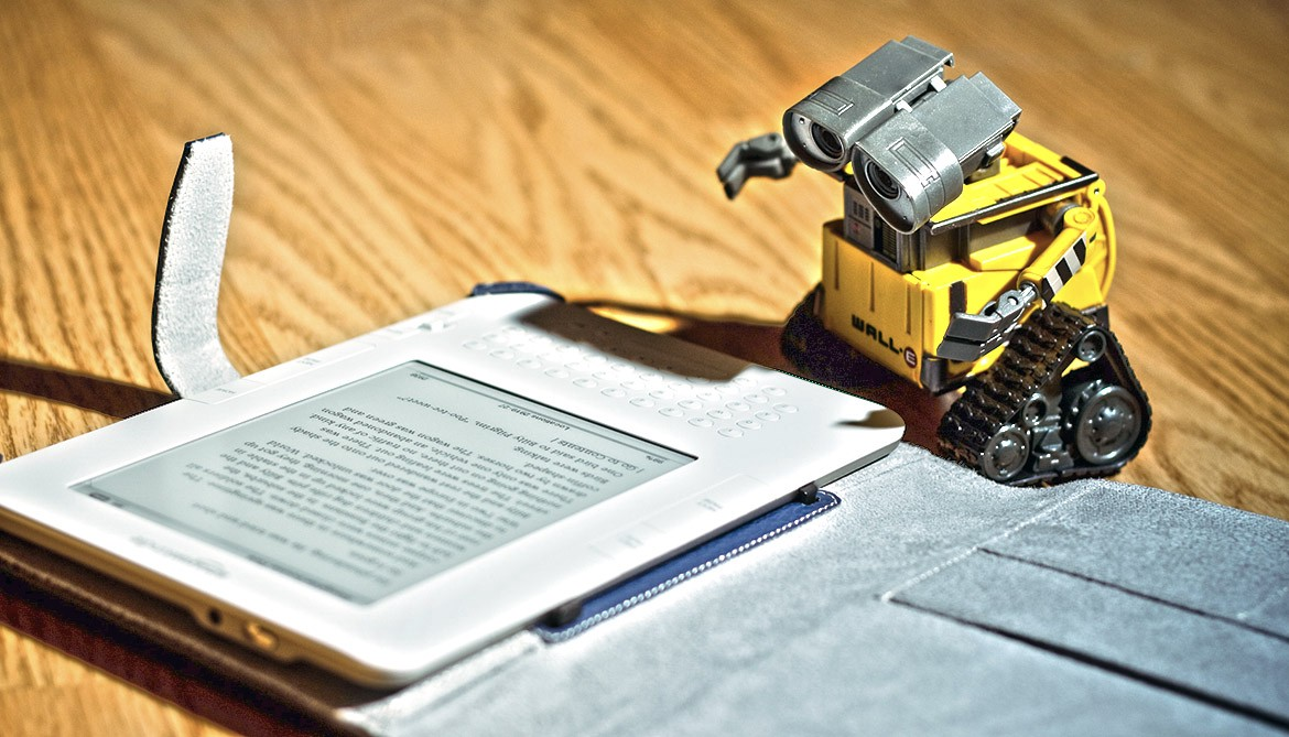 toy robot looking like it is reading from a Kindle device