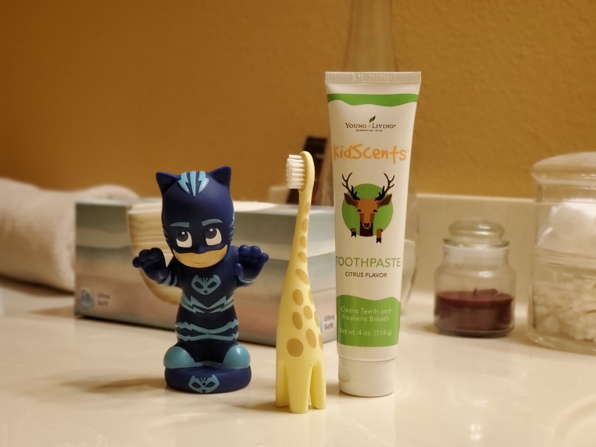 A giraffe-themed child's toothbrush, children's toothpaste, and a PJ Masks bath toy.