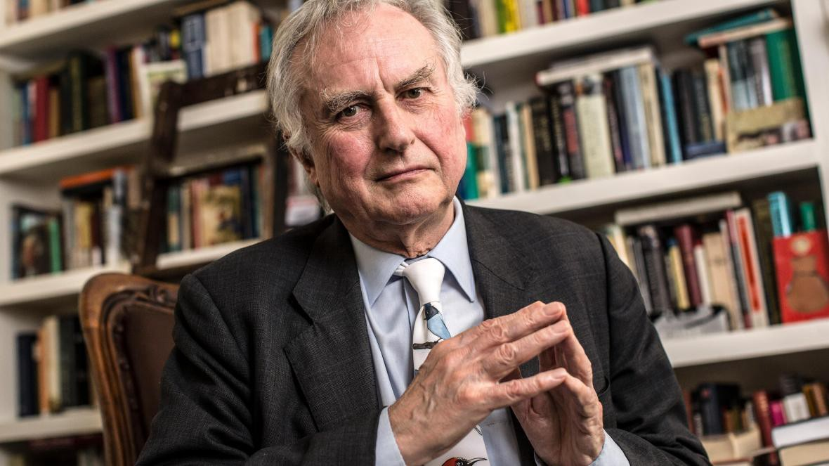 Richard Dawkins sitting on a chair with a bookshelf in the background.