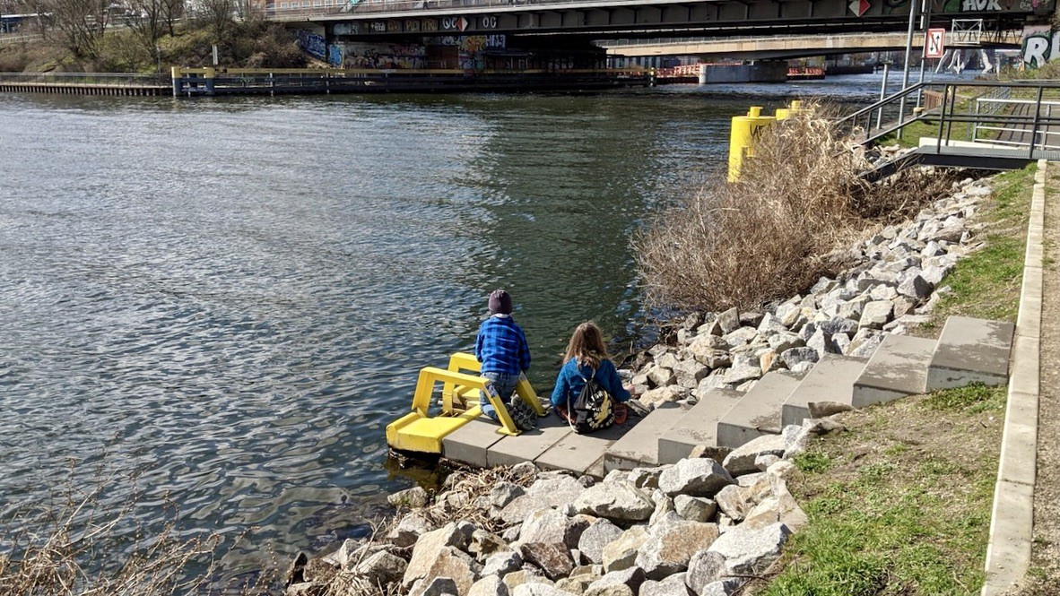 Two children sitting by a river near to two bridges.