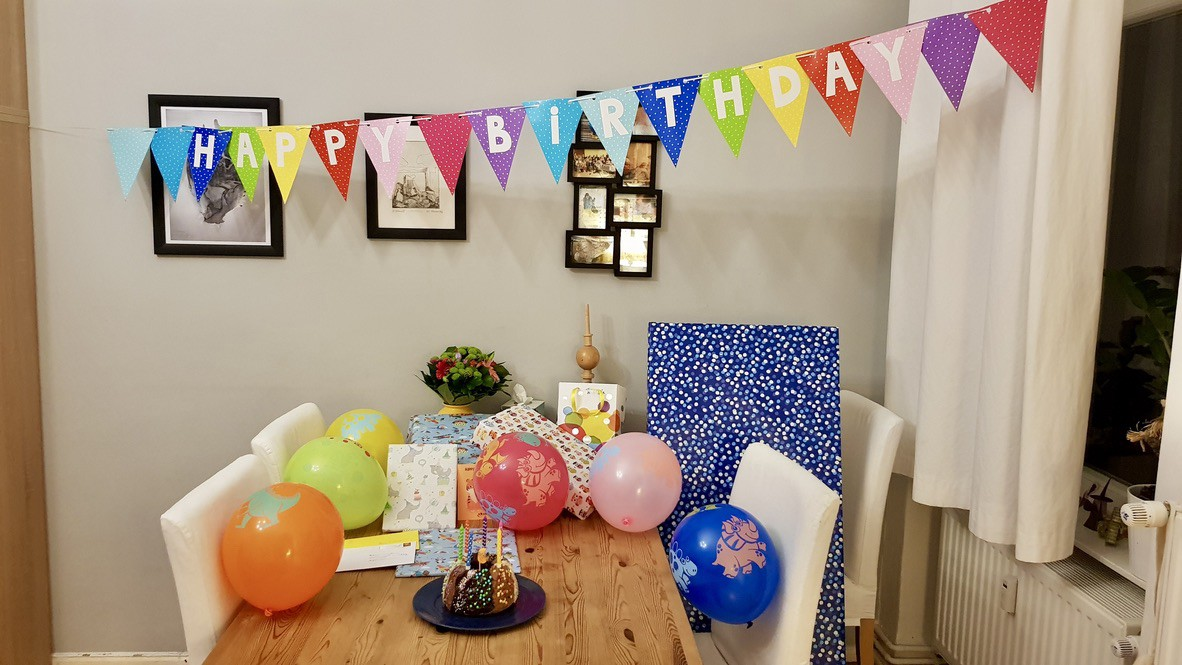 """A table with wrapped gifts, balloons and a cake. A banner above reads """"Happy Birthday."""""""