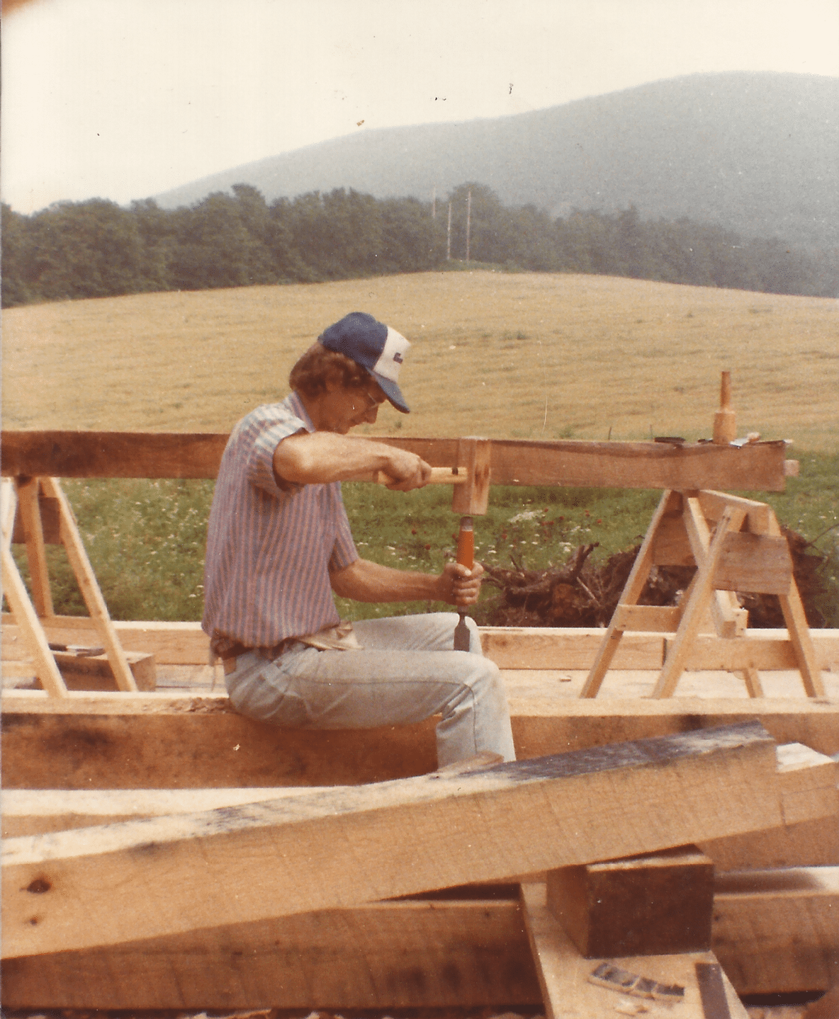 My father carving a beam while building our house