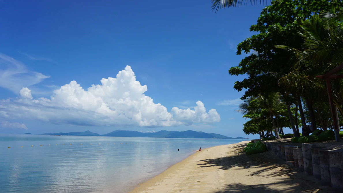 An uncrowded beach in Koh Samui. There is blue water and golden sand, and there are mountains in the distance.