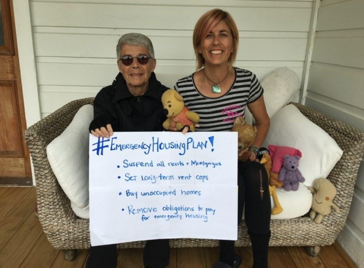 Two women, one older, one younger holding a sign supporting the Emergency Housing Plan.