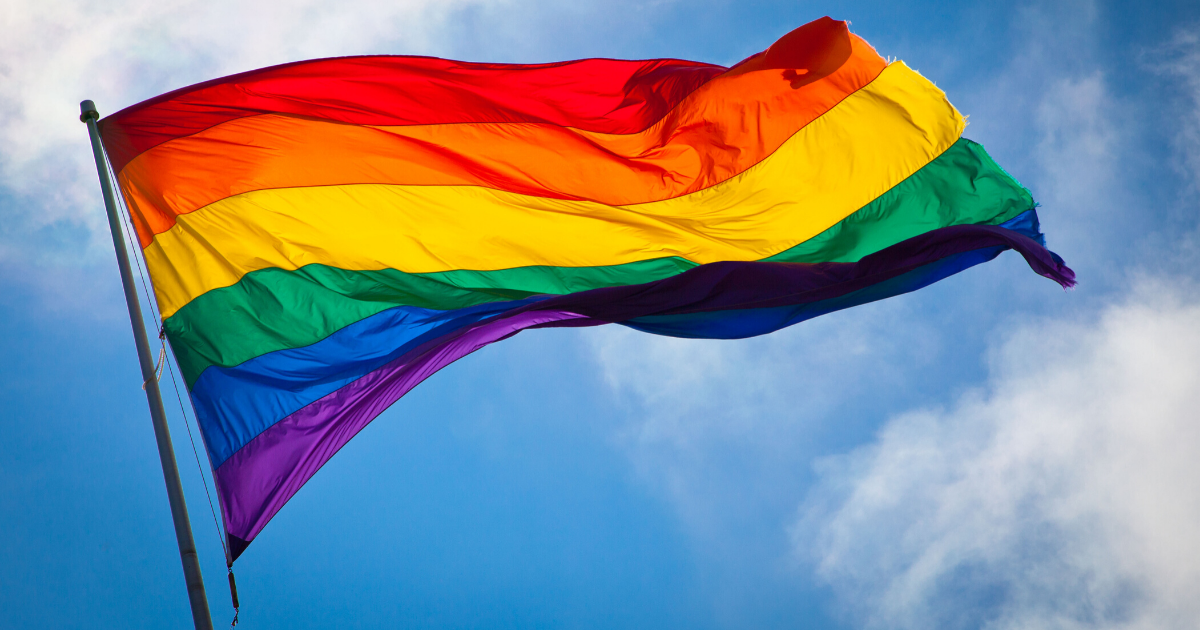 A rainbow flag flying in the wind