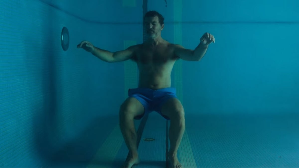 Antonio Banderas in a blue bathing suit, holding his breath underwater and floating