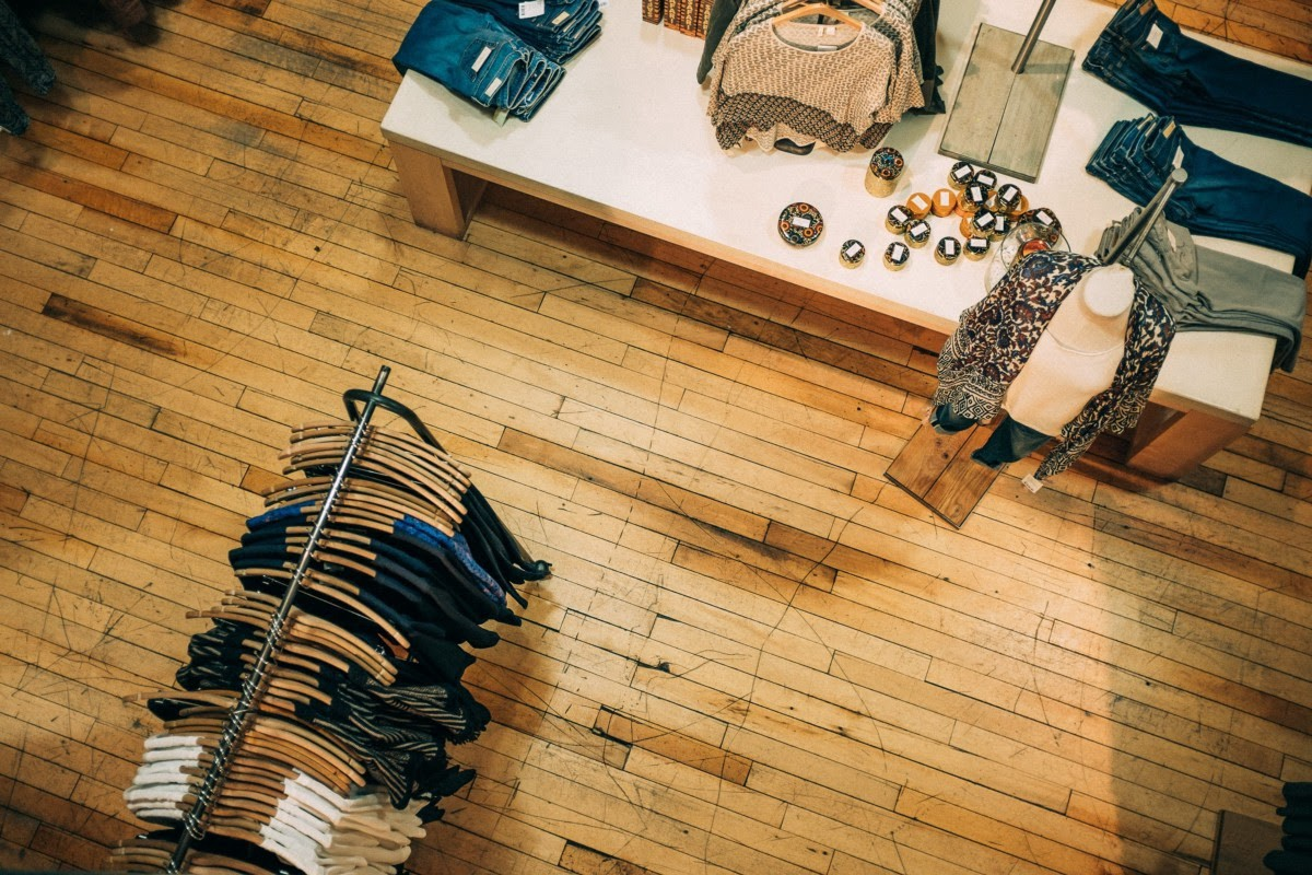 Interior of a retail space with light hardwood flooring, a clothing rack, and a table with accessories.