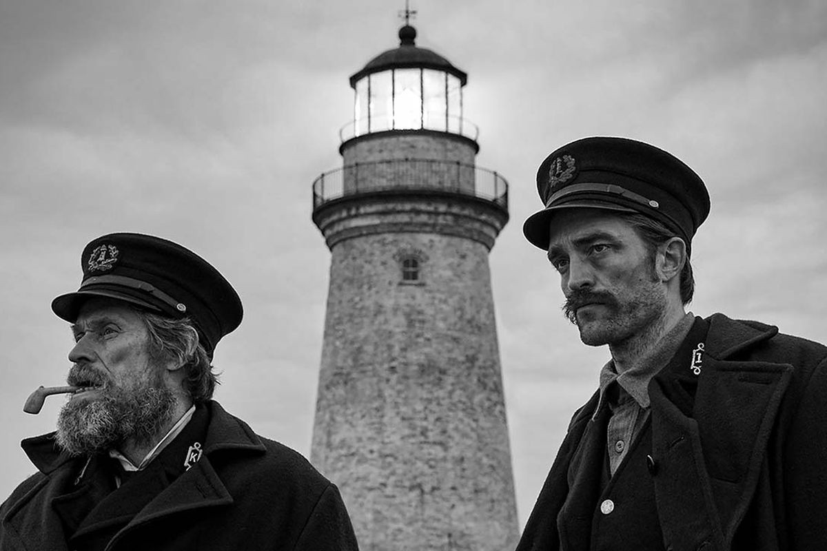 Willem Dafoe and Robert Pattinson in a black and white photo, wearing old-timey uniforms in front of a lighthouse