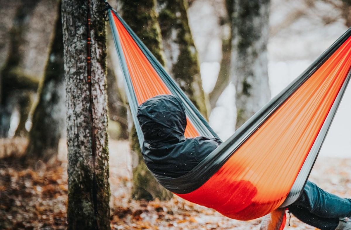 A hooded person sitting in an orange hammock in the woods.