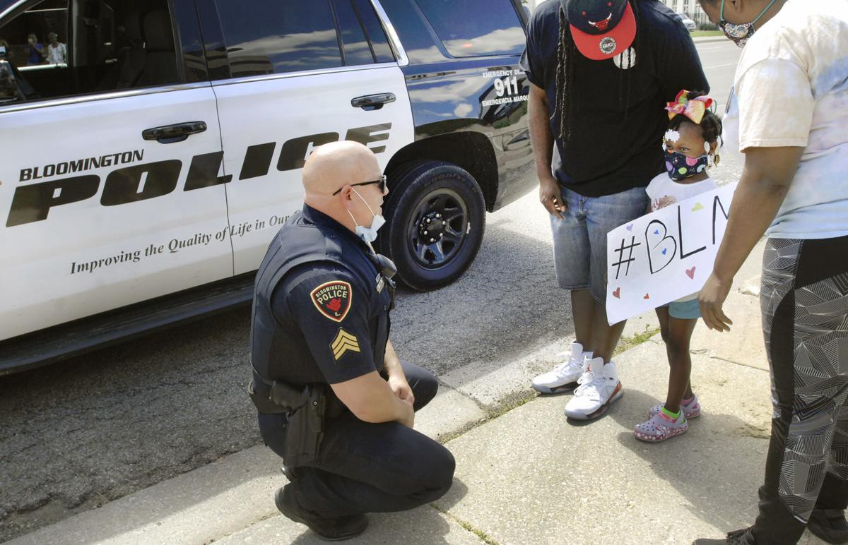 "A Bloomington, IL officer crouches in street to talk with small black girl carrying BLM (Black Lives Matter"" poster."