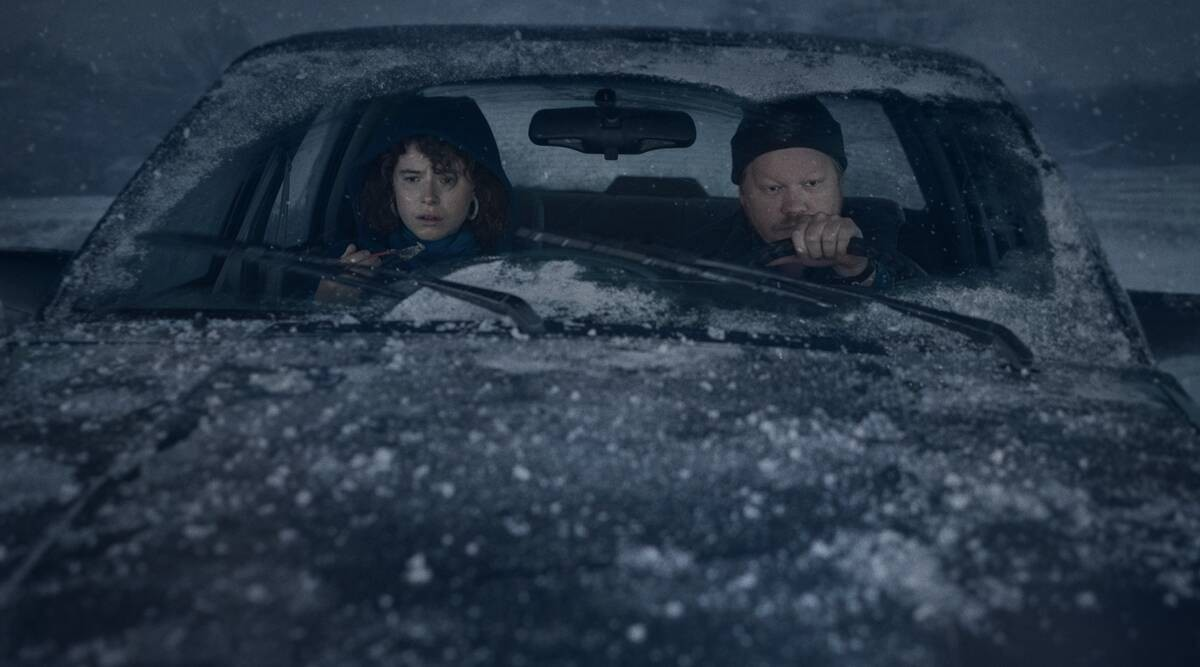 Two characters sitting in a car that's covered in snow except for where the windshield wipers have cleared it off.